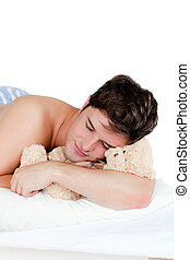 young man in pyjamas sleeping with a teddy-bear lying on his bed during the morning