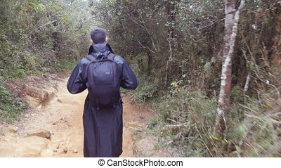Young man in raincoat going on wood trail during travel. Hiking guy with backpack walking in tropical wet forest. Follow to male tourist stepping on the jungle path. Rear back view