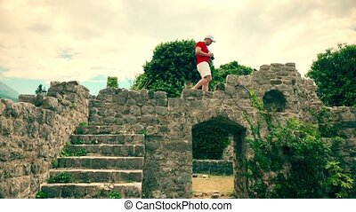Young man in red tshirt photographing ancient ruined...