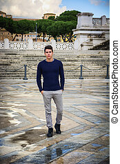 Young man in Rome in front of Vittoriano monument standing