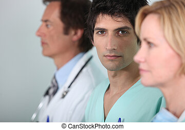 Young man in scrubs with other members of the medical staff
