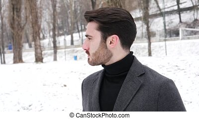 Young man in snowy city park