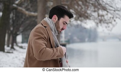 Young man in snowy city putting on gloves - Handsome young...