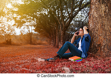 young man in stress situation when talking on mobile phone in park