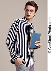 Young man in striped shirt posing with a book on gray background