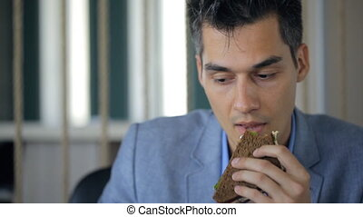 Young man in suit eats sandwich from rye bread and vegetables, drinking tea from a mug.