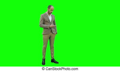 Young man in suit sending text messages on his phone on a Green Screen, Chroma Key.
