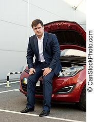 man in suit sitting on broken car with open hood