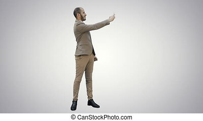 Young man in suit taking selfies on the phone on white background.