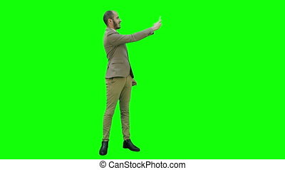 Young man in suit taking selfies on the phone on a Green Screen, Chroma Key.