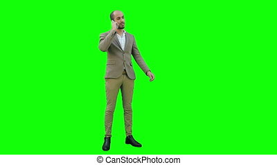 Young man in suit talking on the phone and actively gesturing on a Green Screen, Chroma Key.