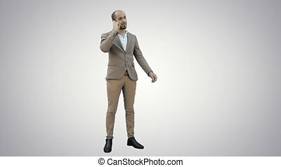 Young man in suit talking on the phone and actively gesturing on white background.