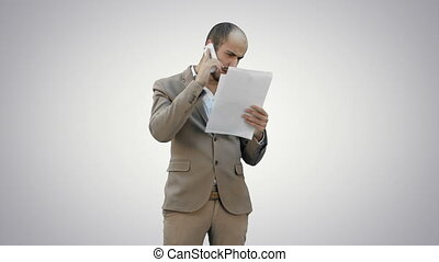 Young man in suit talking on the phone and holding papers on white background.