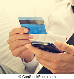 young man in suit using his credit card online