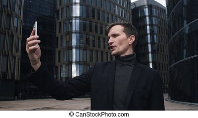 Young man in suit using smartphone. Glass business centre building at background