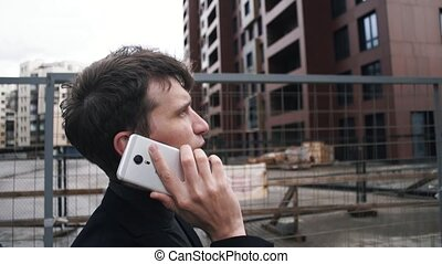 Young man in suit using smartphone. House under construction at background