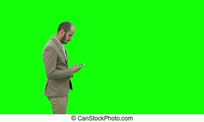 Young man in suit walking and sending text message on mobile phone on a Green Screen, Chroma Key.