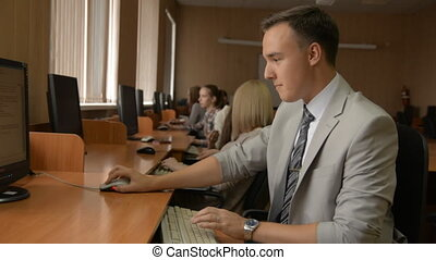 Young man in suit working at computer