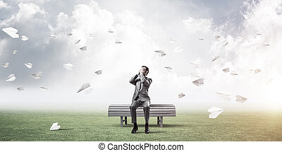 Young man in summer park on bench do not want to see anything