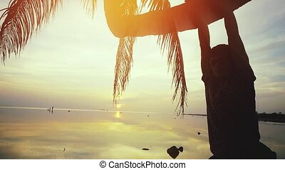 Young man in sunglasses hangs on a palm tree at sunset on the beach. slow motion. 1920x1080