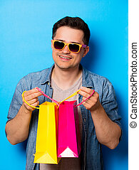 Young man in sunglasses holding a shopping bags