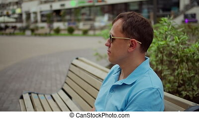 Young man in sunglasses is resting while sitting on a bench on a blurred background of the city, camera movement