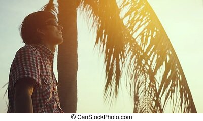 Young man in sunglasses rests sitting on a palm tree, above the water against the backdrop of the sea and sunset, slow motion. 1920x1080