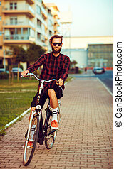 Young man in sunglasses riding a bike on city street - Young...