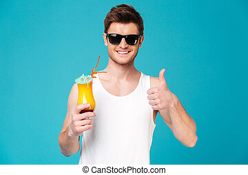 Young man in sunglasses showing cocktail and thumb up