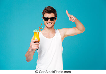 Young man in sunglasses showing cocktail