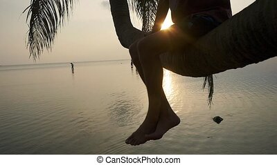 Young man in sunglasses sits on a palm tree waving his legs...