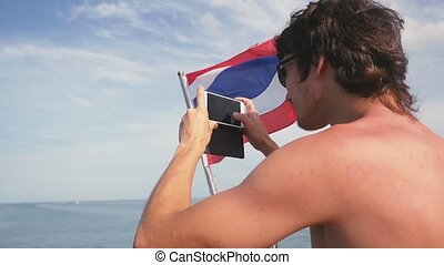 Young man in sunglasses taking selfie with Thai flag while...