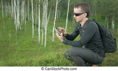 Young man in sunglasses touch Tablet PC. Against the background of beautiful nature: green trees and grass
