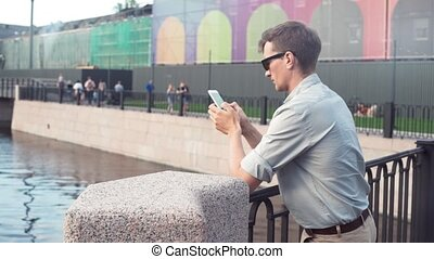 Young man in sunglasses using smartphone standing at city park