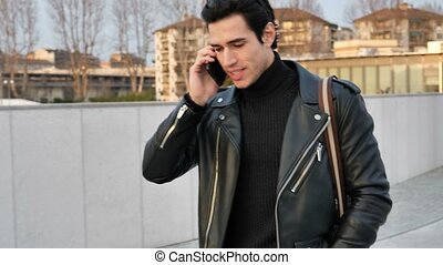 Young man in talking on cellphone outdoor in city