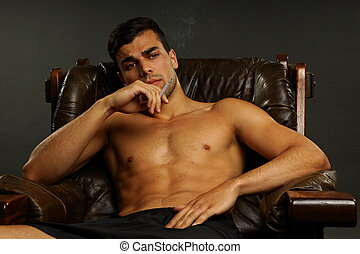 Young man in the chair smokes