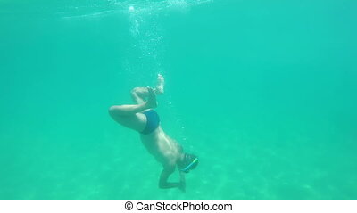 Young man in the clear ocean water driving with snorkel