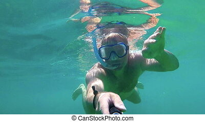 Young man in the clear ocean water driving with snorkel,