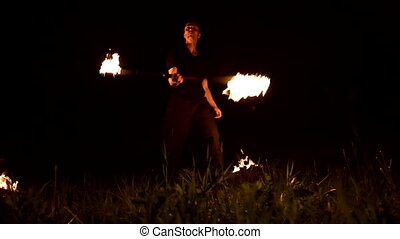 Young man in the dark depicts rotating burning torch. Fire ...