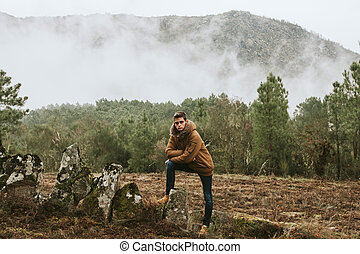 young man in the forest looking at the landscape