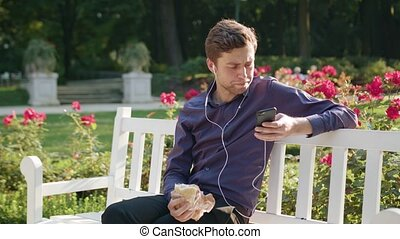 Young Man in the Park Listening to Music and Eating