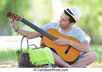young man in the park tuning his guitar