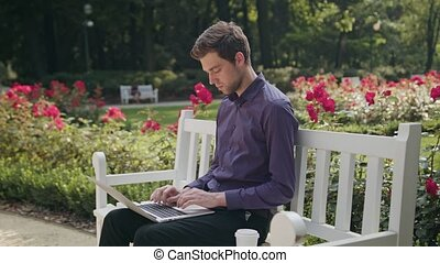 Young Man in the Park Using a Laptop and Drinking