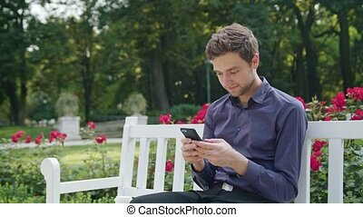 Young Man in the Park Using a Phone