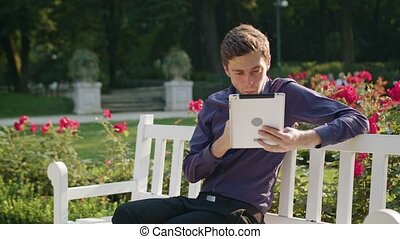 Young Man in the Park Using a Tablet and Eating