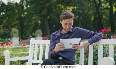 Young Man in the Park Using a Tablet