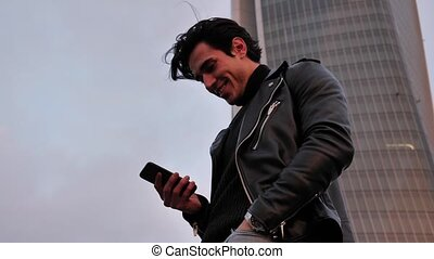 Young man in using cellphone outdoor in city
