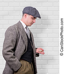 young man in vintage clothes, looking watch, 1940
