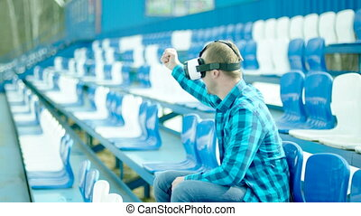 Young man in VR glasses rooting for a team on the tribune