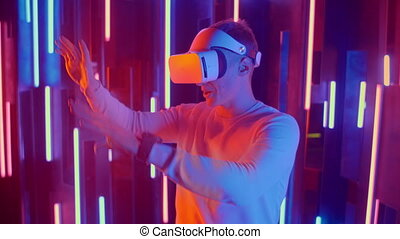 Young Man in VR headset looks around and wonders how amazing. Virtual reality helmet